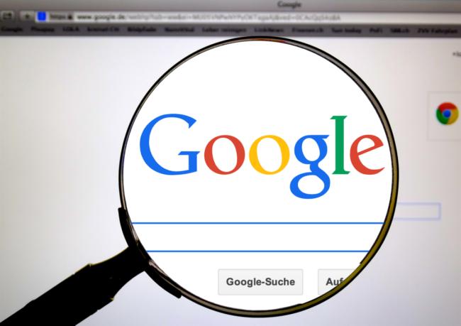 Das Google-Logo über dem Eingabefeld der Google-Suchmaschine wird durch eine Lumpe vergrößert dargestellt.