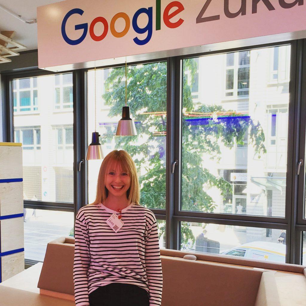 Ein blondes Mädchen steht unter dem Logo der Google Zukunftswerkstatt in Hamburg. Die Räumlichkeiten sind lichtdurchflutet und in den Farben (blau, rot, grün, gelb) des Google-Logos gestaltet.